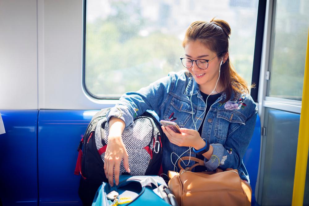 電車でスマホを楽しむ女性