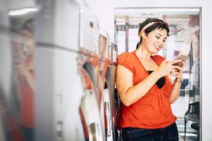 コインランドリーの空き時間にスマートフォンを楽しむ女性