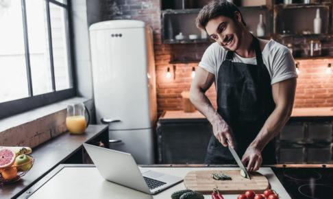 料理をしながらPCを見る男性